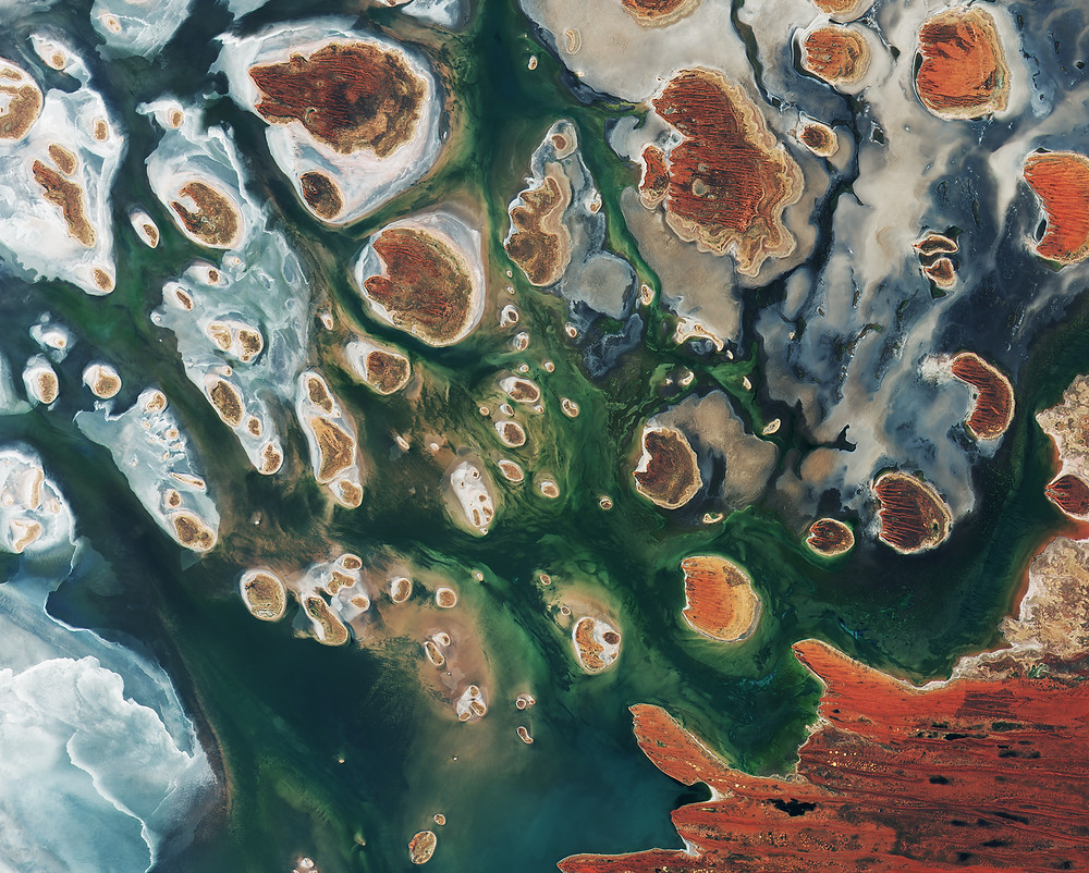 Dozens of orange islands are starkly contrasted against a blue green lake in this overhead satellite image.