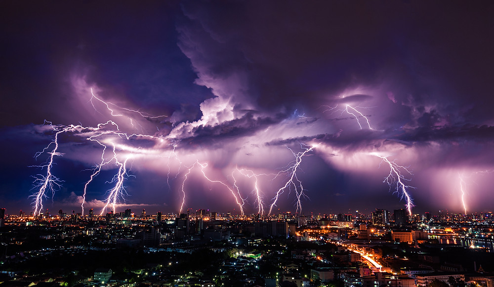 Nine bolts of lightning light up a purple sky as they reach into an illuminated city.