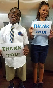 2 kids with thank you signs.jpg