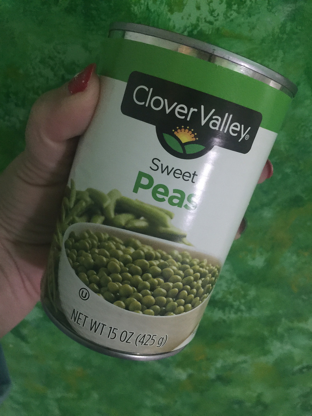 Lady holding a can of clover valley peas
