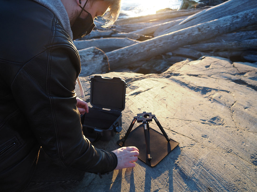 View over the shoulder of a scientist crouching down at a beach and setting up the imaging system