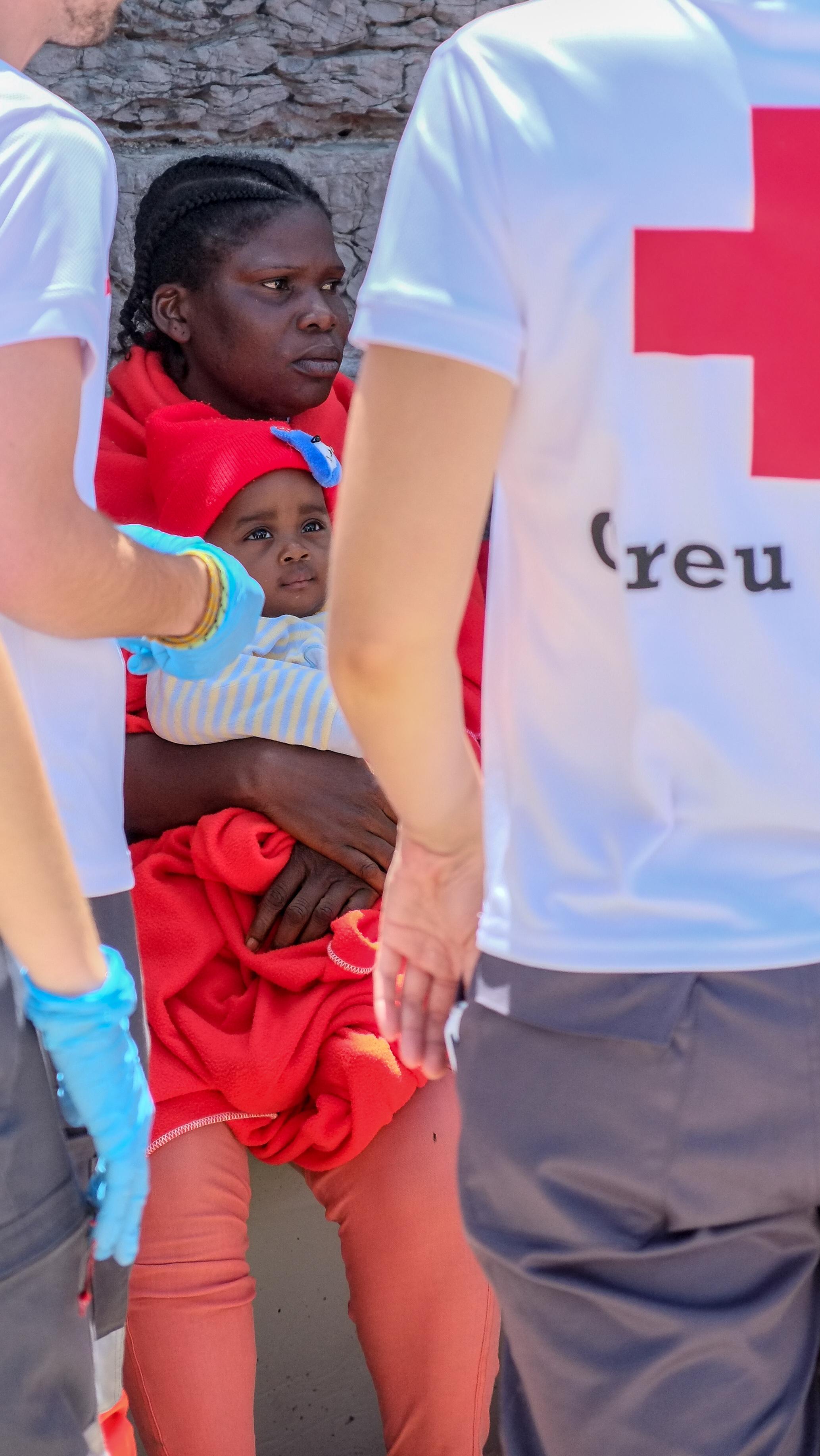 Eine Mutter hält ihr Baby im Arm; beide waren kurz zuvor aus dem Mittelmeer gerettet wurden