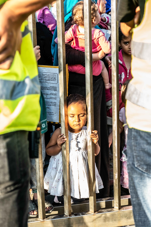 Ein Mädchen am Zaun einer NGO, die Flüchtlingen hilft