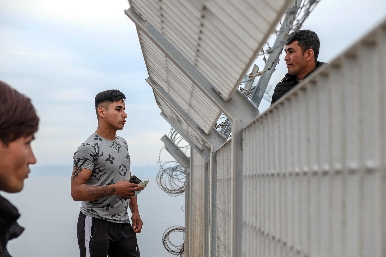Zwei Migranten unterhalten sich durch einen Zaun