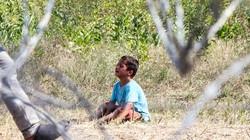 Ein Junge auf dem Boden in einem Flüchtlingslager