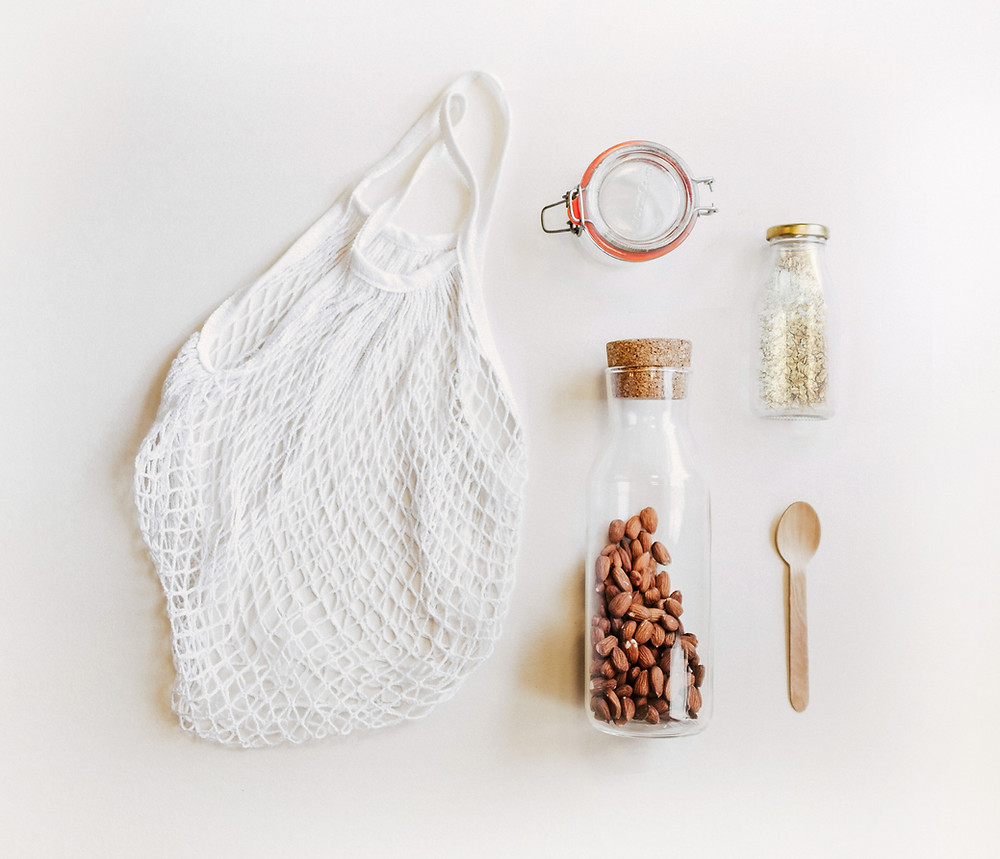 Flatlay of cotton bag, mason jar and bottles with almonds and grains