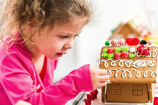 Kids decorating small gingerbread houses