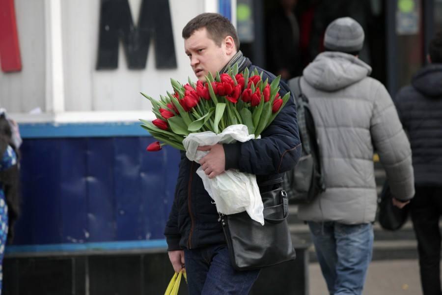 Мужчины несут цветы в подарок.