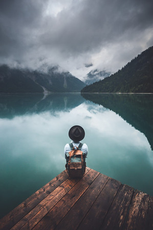 Man with hat standing on dock by the lake, Plansee, Tirol, Austria