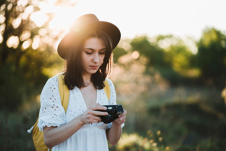 Fashioned young woman holding vintage camera