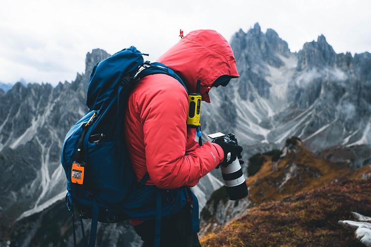 Photographer checking photos on DSLR, Dolomites, Italy