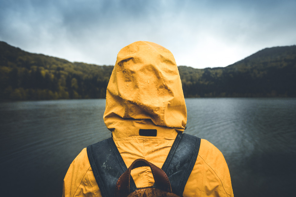 Active outdoors people lifestyle. Rear view of a hiker enjoying rainy weather. Outdoors adventure trek activity, hiker wearing yellow waterproof raincoat sportswear clothes
