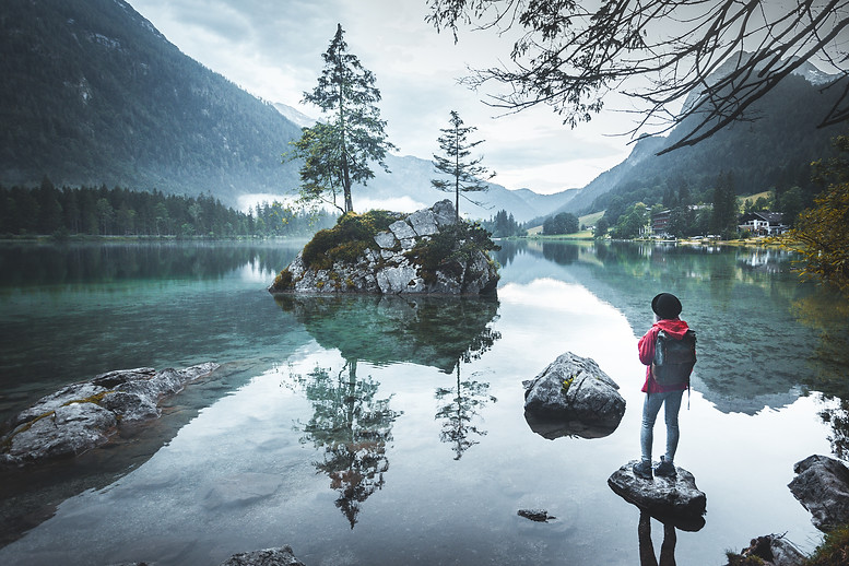 Young woman hiker sitting by the lake in autumn, Hintersee, Bayern