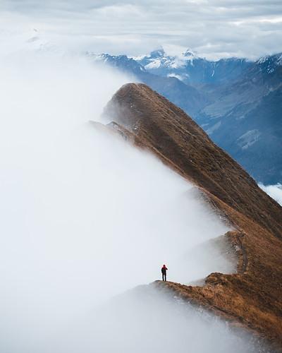 Hiker standing on ridge with fog