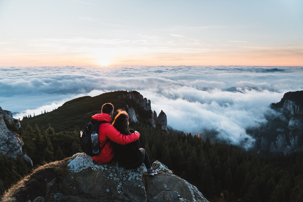 Young couple enjoying sunrise at mountain summit