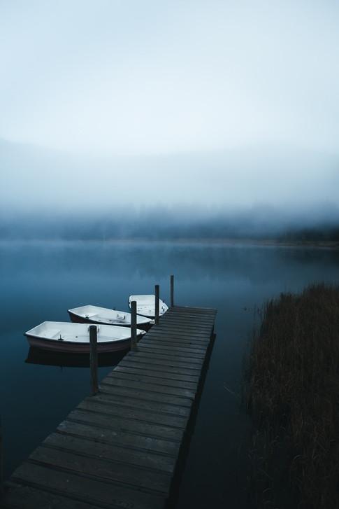 Boats on the lake near jetty on a misty
