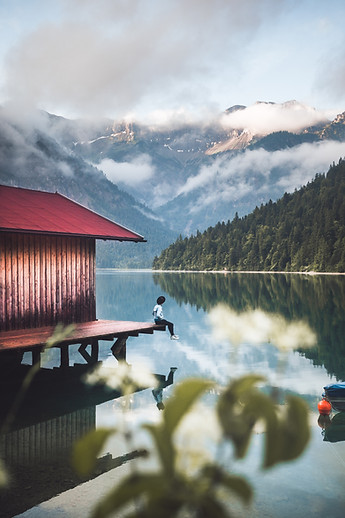 Young male with hat sitting on the dock of a rustic wooden hut at mountain lake Plansee, Tyrol, Austria