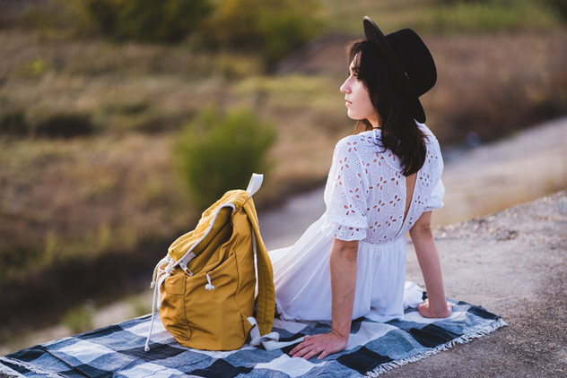 Back view of stylish young woman sitting