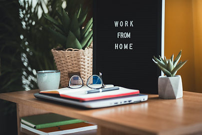 Letter board with work at home words. Eyeglasses, notebook and pen at desk with potted plants and a coffee mug in background. Concept work from home
