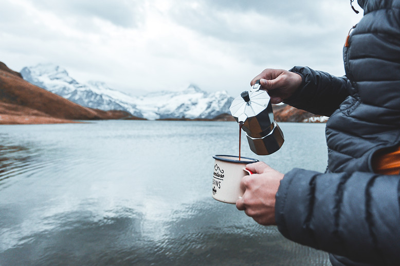 Human hands  of a man traveler pouring coffee into a mug  from an expresso coffe maker. Adventure, travel, hiking and camping concept at Bachalpsee Lake, Switzerland