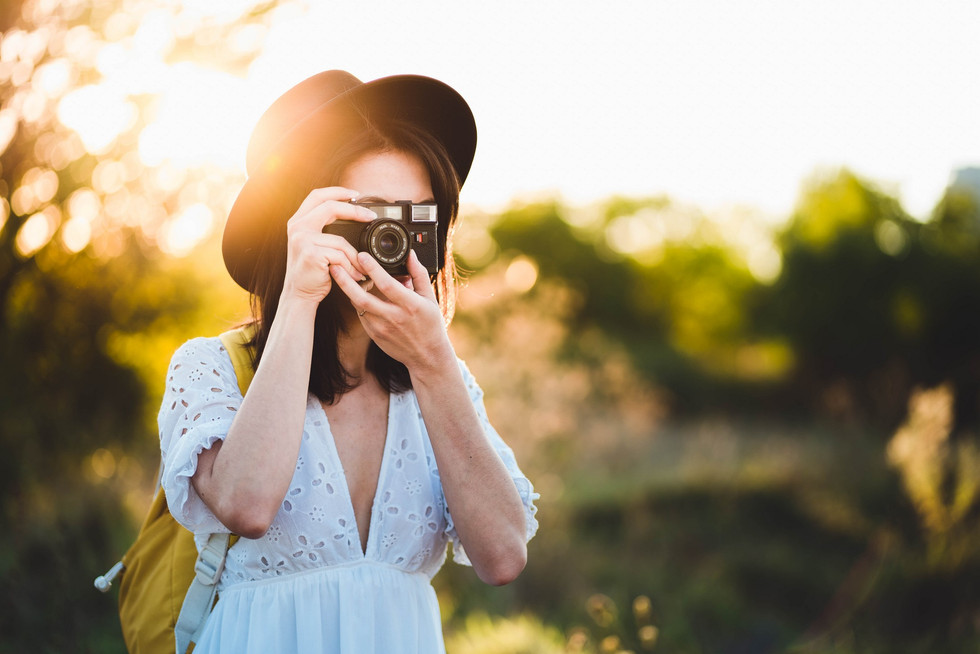 Fashioned young woman taking photos with vintage camera