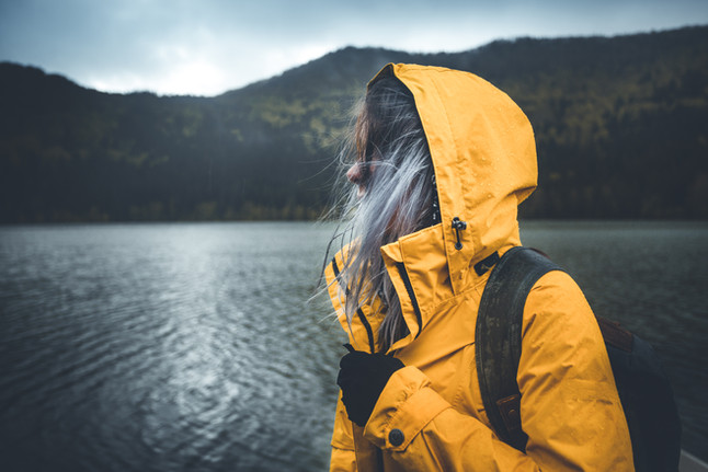 Active outdoors people lifestyle. Close up view of a hiker enjoying rainy weather. Outdoors adventure trek activity, hiker wearing yellow waterproof raincoat sportswear clothes