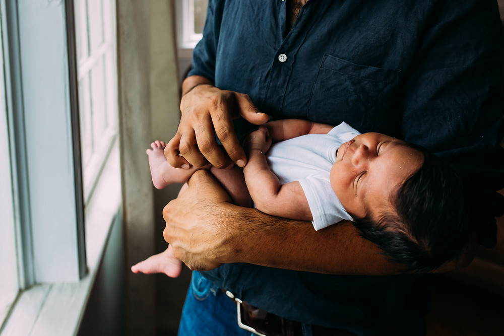 newborn baby in dad's arms