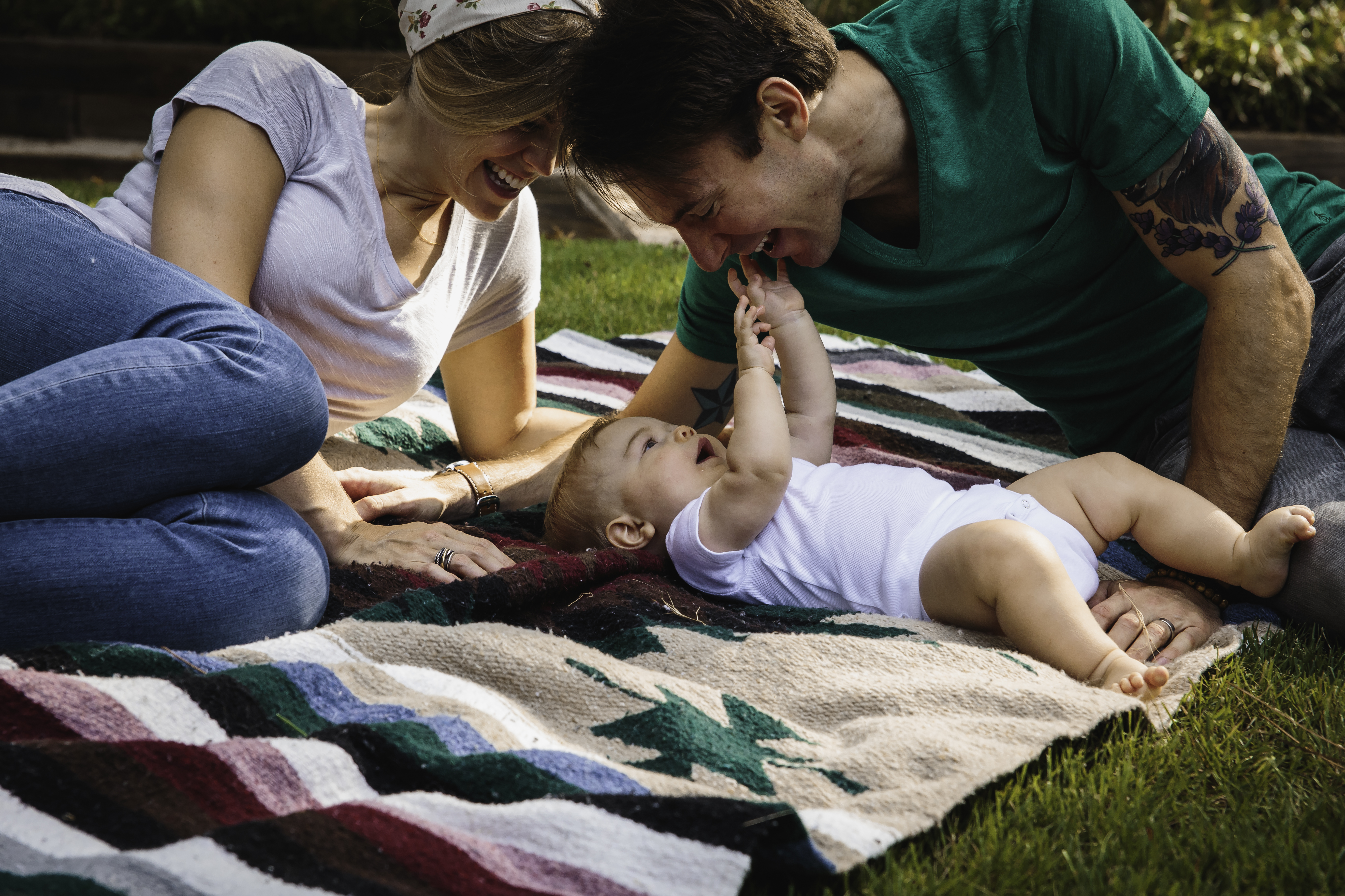Mom and Dad on a blanket with baby