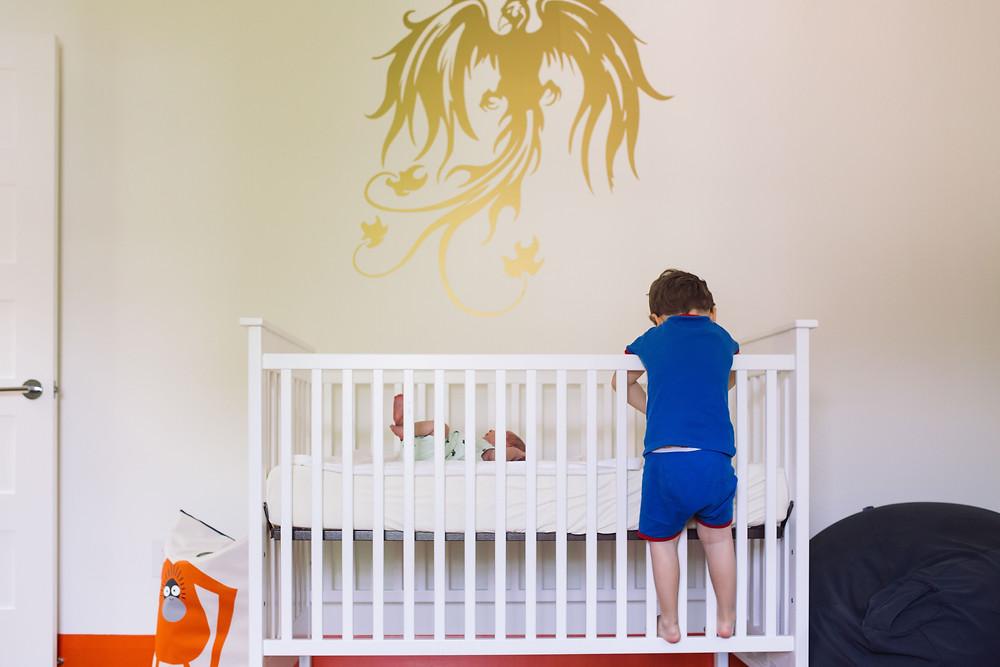 newborn and big brother in a nursery