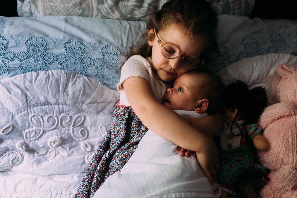 Sister holding newborn brother