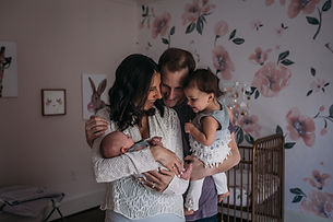 Famiy in nursery wth newborn baby