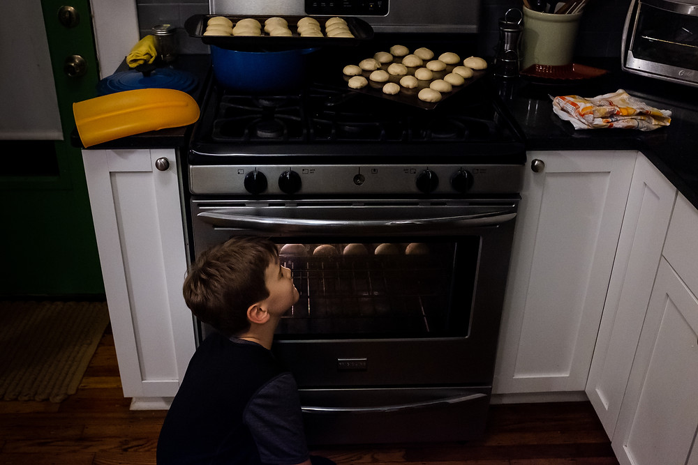Boy watching the oven while rolls bake