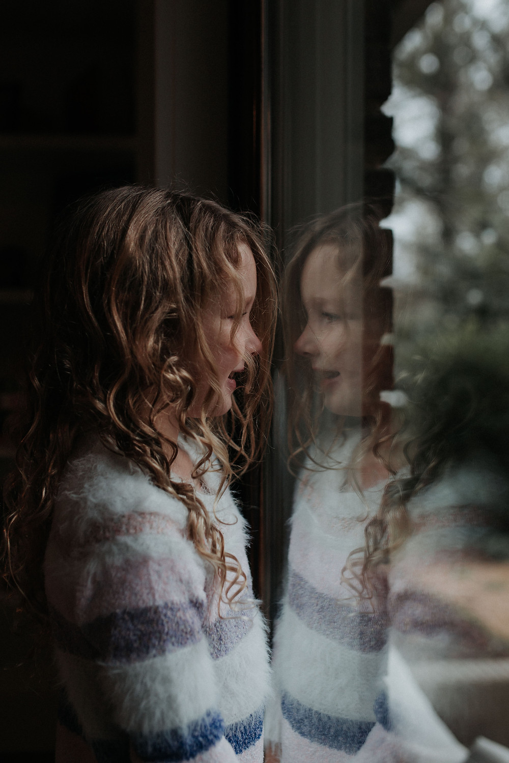 A little girl looking out the window
