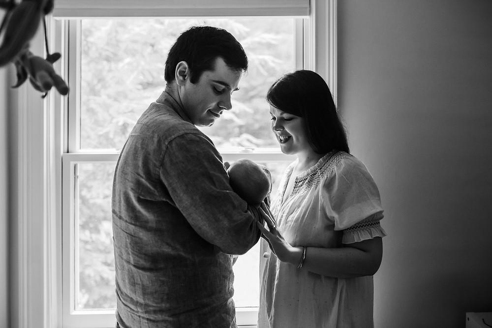 mom and dad holding newborn baby