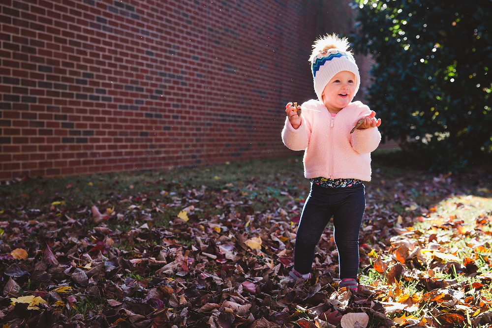 baby girl in leaves