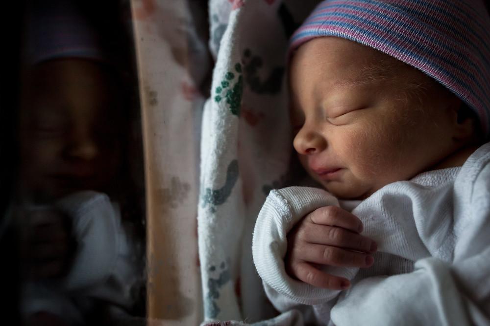 newborn baby in hospital bassinet