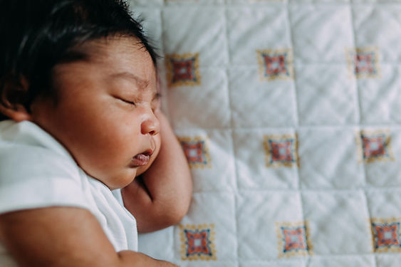 Sleeping newborn baby on bed