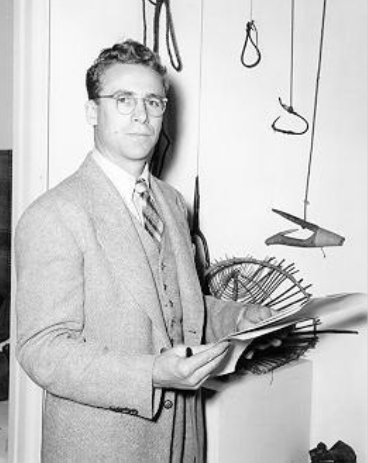 Harry Hawthorn posing with artifacts