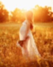 Beautiful pregnant woman in a field wear