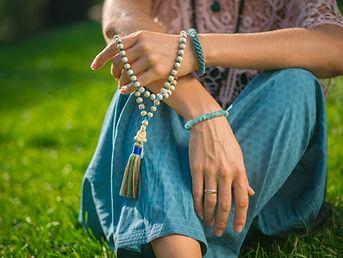 Woman, lit hand close up, counts Malas,