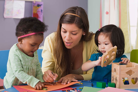 early childhood educator with two children doing activities