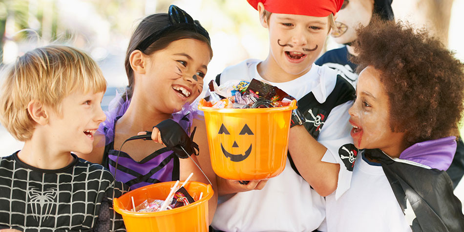 Children in Halloween Costumes With Candy