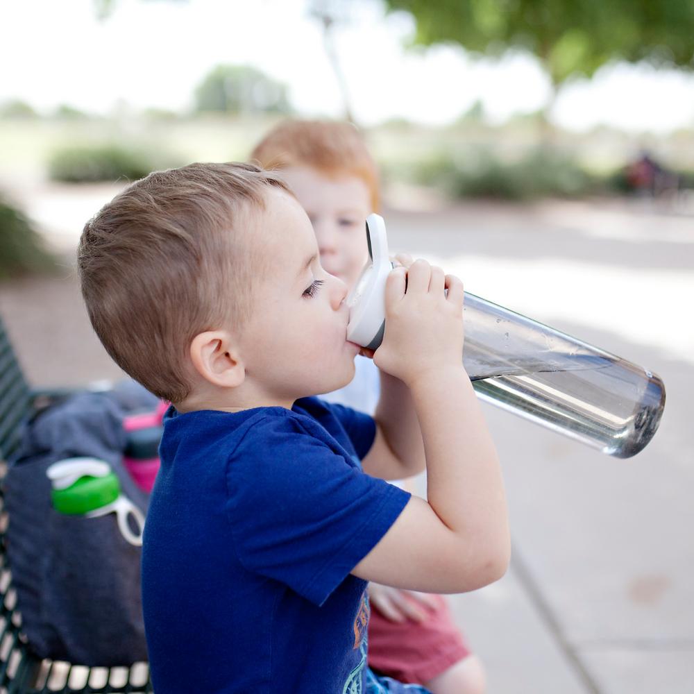 little boy drinking from water bottle