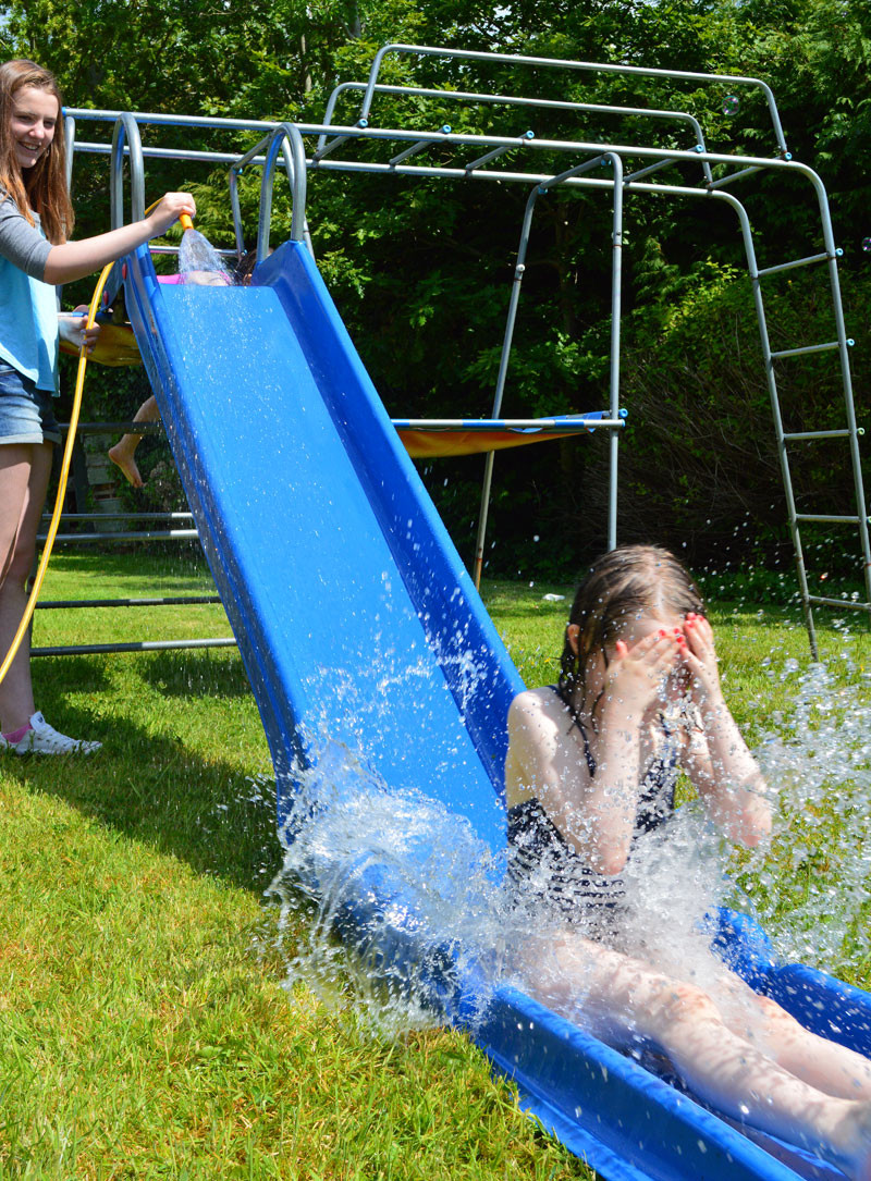 Parents and children using playground slide and water to create waterslide