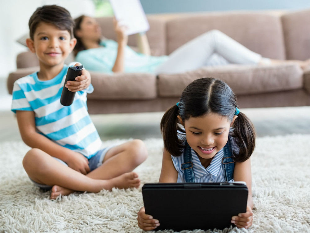 children on rug watching ipad and tv