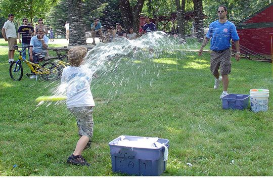Father and son playing baseball with water balloons