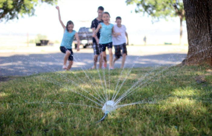 Children playing with homemade water sprinkler in the backyard