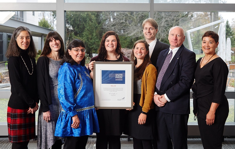 From left to right, Julie Morita, Chandler O'Connell, Vera Gibson, Tina Bachmeier, Holly Marban, Doug Osborne, Loyd Platson, and Sheri Johnson, on Tuesday, Nov. 12, 2019, at the Robert Wood Johnson Foundation Culture of Health Prize Celebration and Learning Event in Princeton, N.J., presenting and accepting Sitka, Alaska's 2019 RWJF Culture of Health Prize award. Morita and Johnson are with the RWJF, while the six others are part of the Sitka Health Summit Coalition. Copyright 2019 Flynn Larsen. Photo courtesy of the Robert Wood Johnson Foundation.
