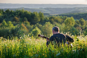 playing guitar, hillside, meadow
