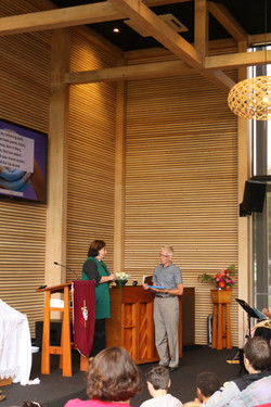 Michael Parker being presented a thank you gift by Rev. Anne